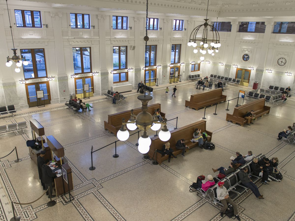 The interior of a train station with people sitting on benches in a large, open space with cathedral ceilings. The walls are white and the floor is tile with a wide pattern of lines creating squares.