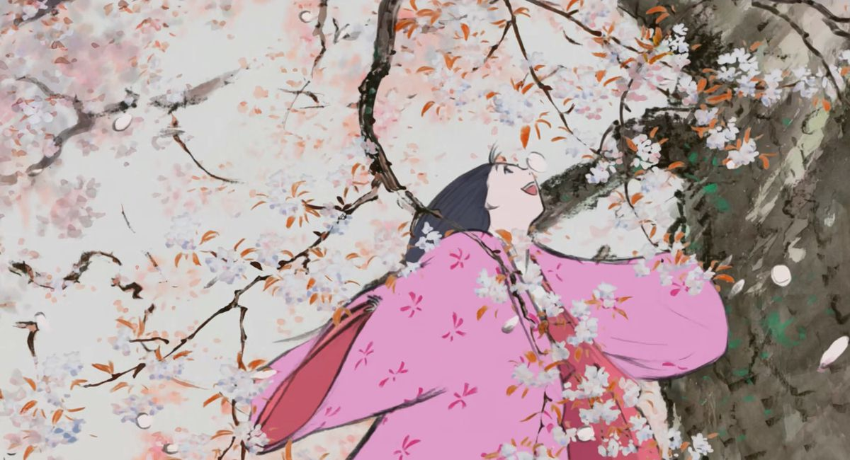 in a scene from the anime film The Tale of the Princess Kaguya, a dark-haired girl in pink robes plays with the branches of a flowering tree