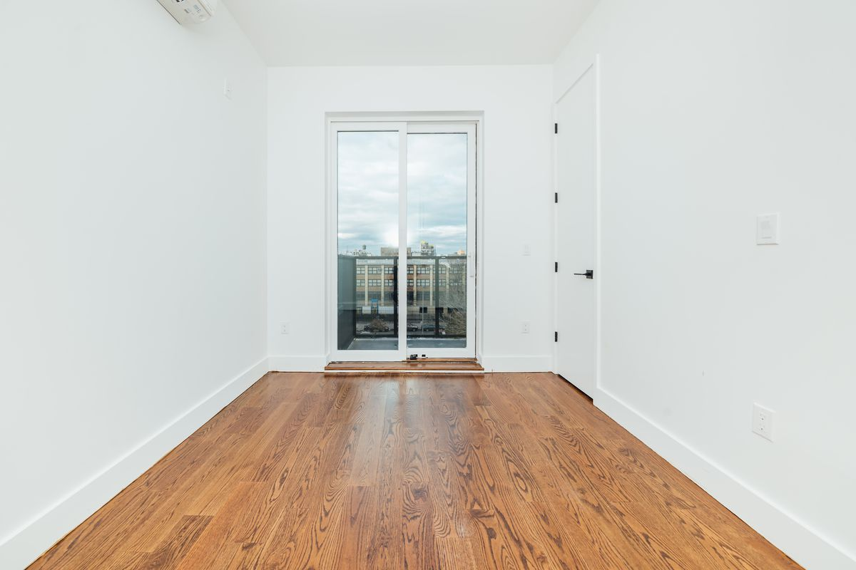 A bedroom with hardwood floors, white walls, and a small glass door that leads to a balcony.