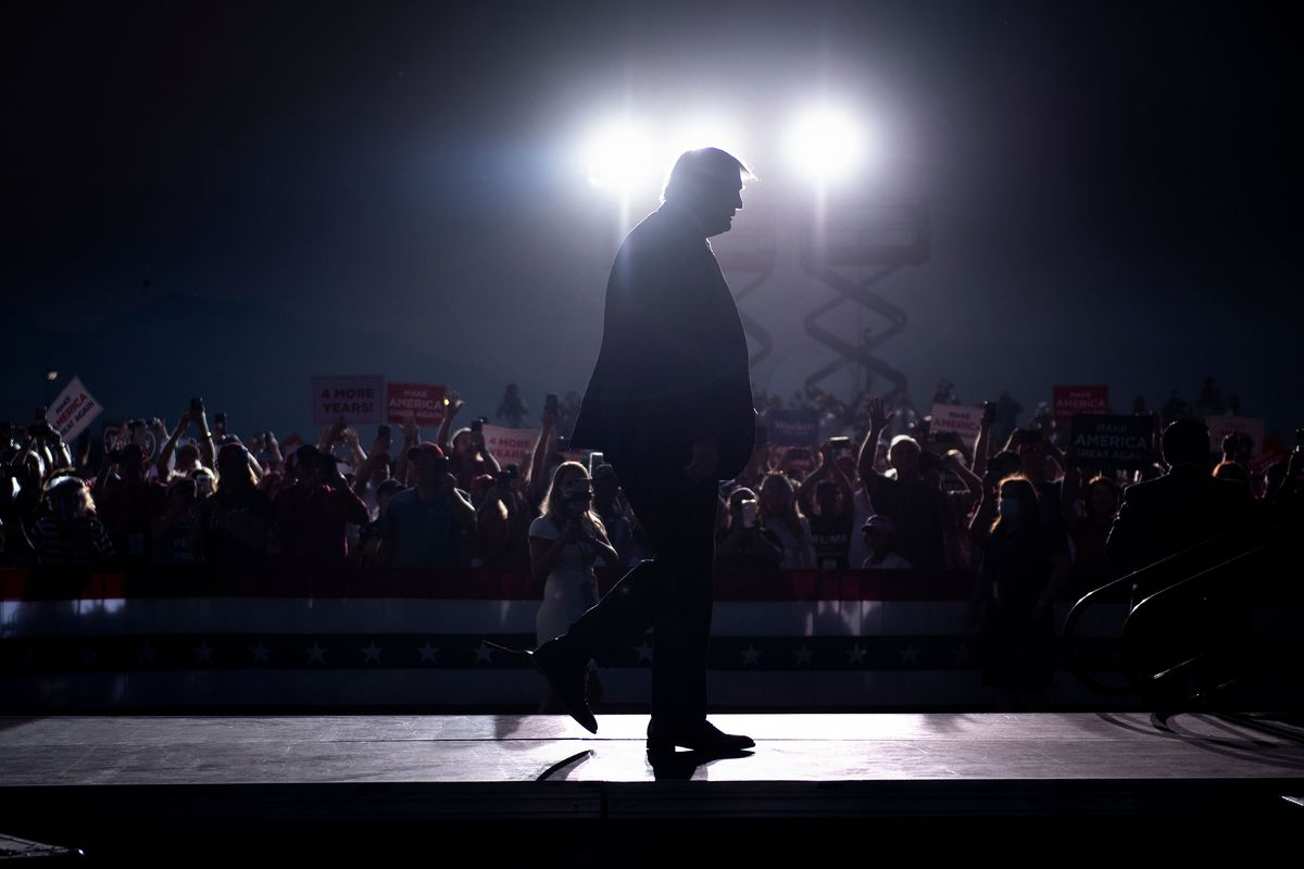 President Trump is silhouetted against bright lights as he walks in front of a gathered crowd.