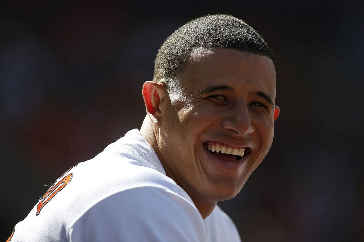 Manny Machado smiles and angelic light shines down from above.