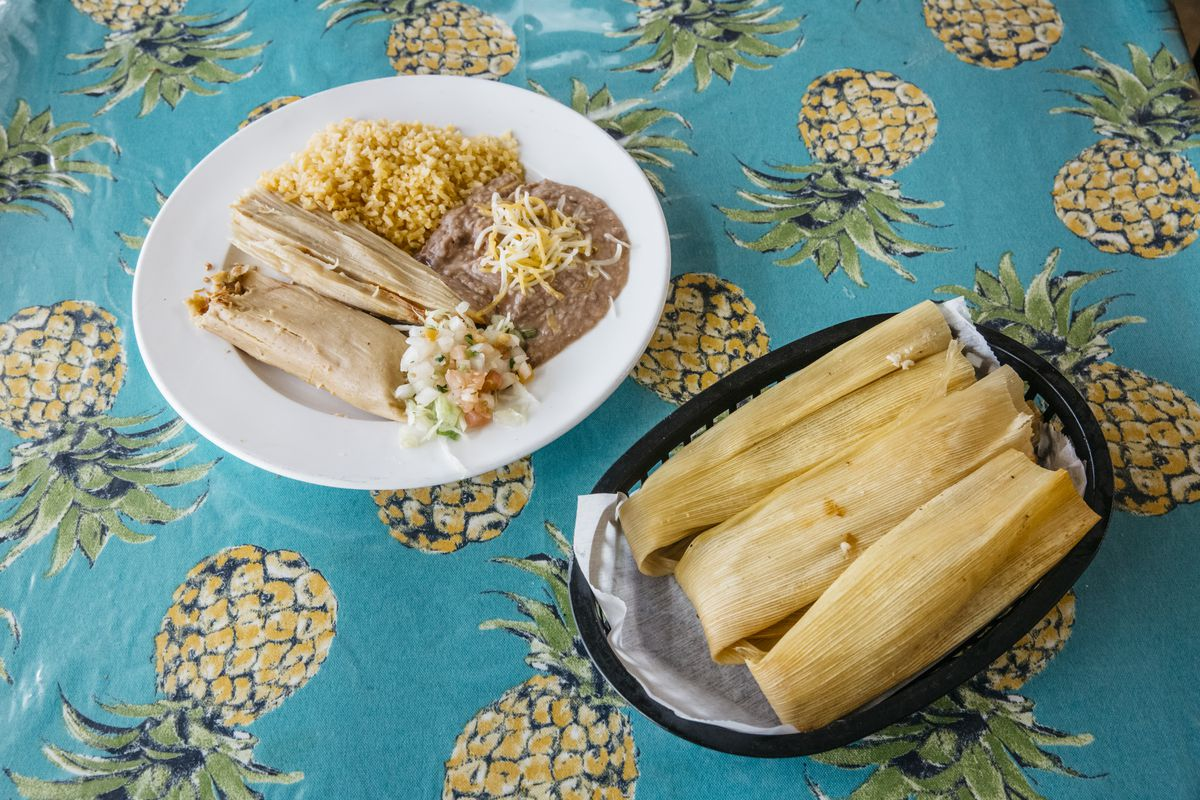 One white plate with a tamale alongside rice and beans sits next to a plastic basket of three unwrapped tamales.