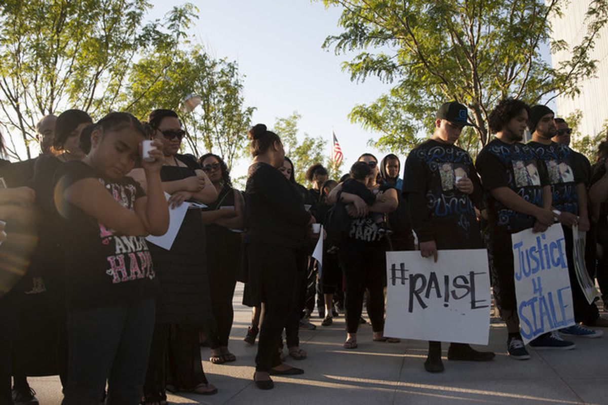 FILE - People listen to a prayer during a vigil for Siale Maveni Angilau, who was shot and killed in federal court by a U.S. marshal on April 2, on the steps of the Federal Courthouse, Wednesday, June 11, 2014.