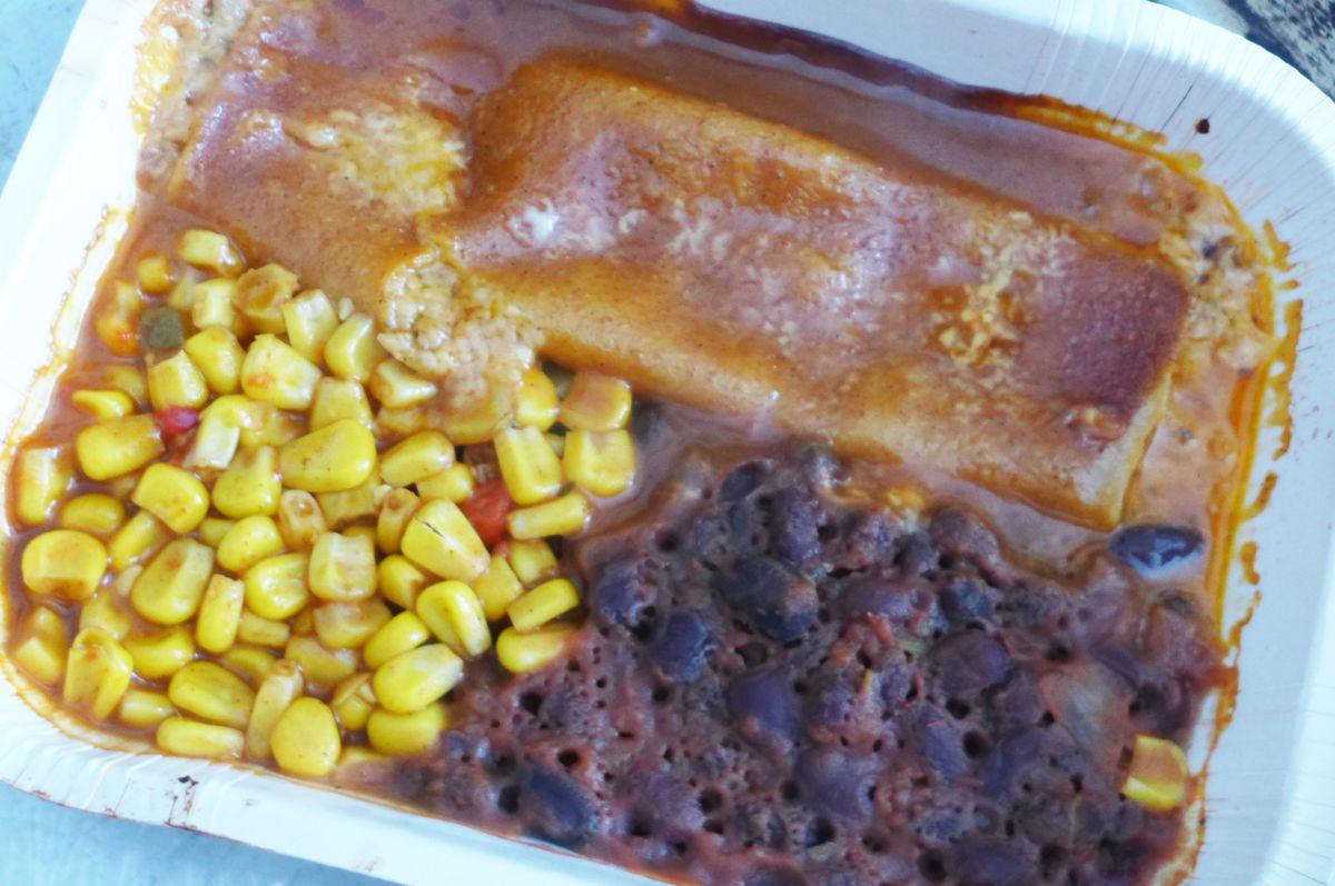 A shriveled enchilada with black beans and kernel corn.