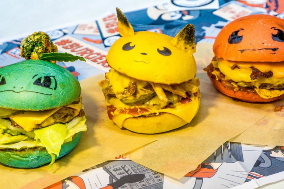 a green bulbasaur burger, a yellow pikachu burger, and an orange charmander burger laid out on yellow tissue paper and a pokemon-themed table
