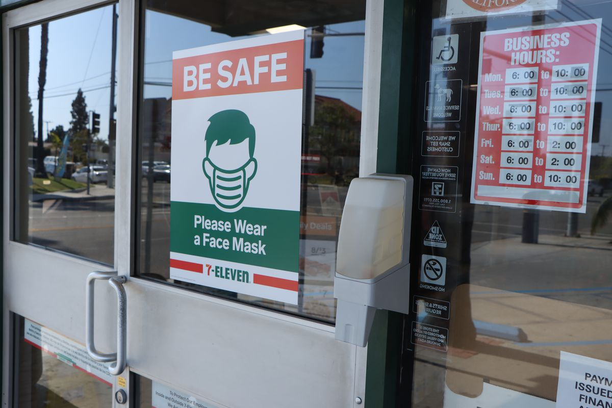 """An orange, white, green, and red sign proclaiming """"Be safe, please where a mask"""" posted to the glass doors of a 7-Eleven market."""