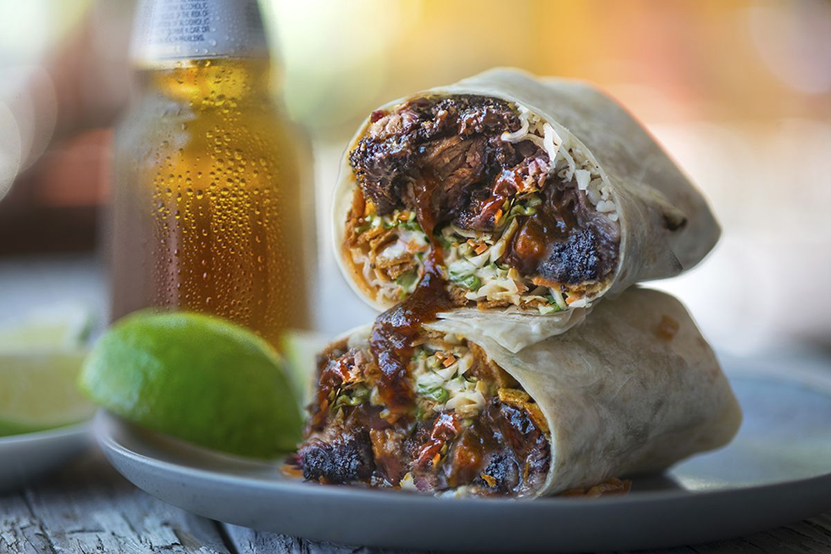 Burnt ends and barbecue sauce peek out from inside of a tortilla made as a wrap, or burrito.