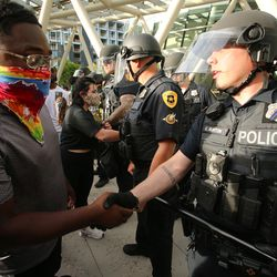 A demonstrator shakes hands with a police officer at the Public Safety Building in Salt Lake City on Monday, June 1, 2020.