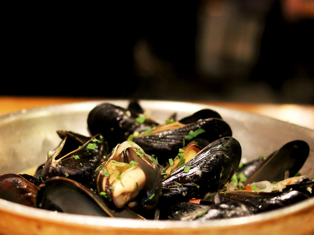 A silver pan is full of steamed mussels