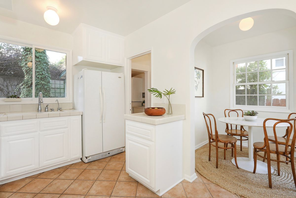 A spacious kitchen with tile counters and a breakfast nook.