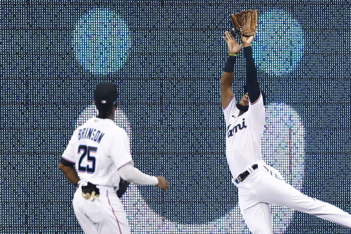 Bryan De La Cruz #77 of the Miami Marlins makes a catch at the wall against the Washington Nationals during the third inning at loanDepot park