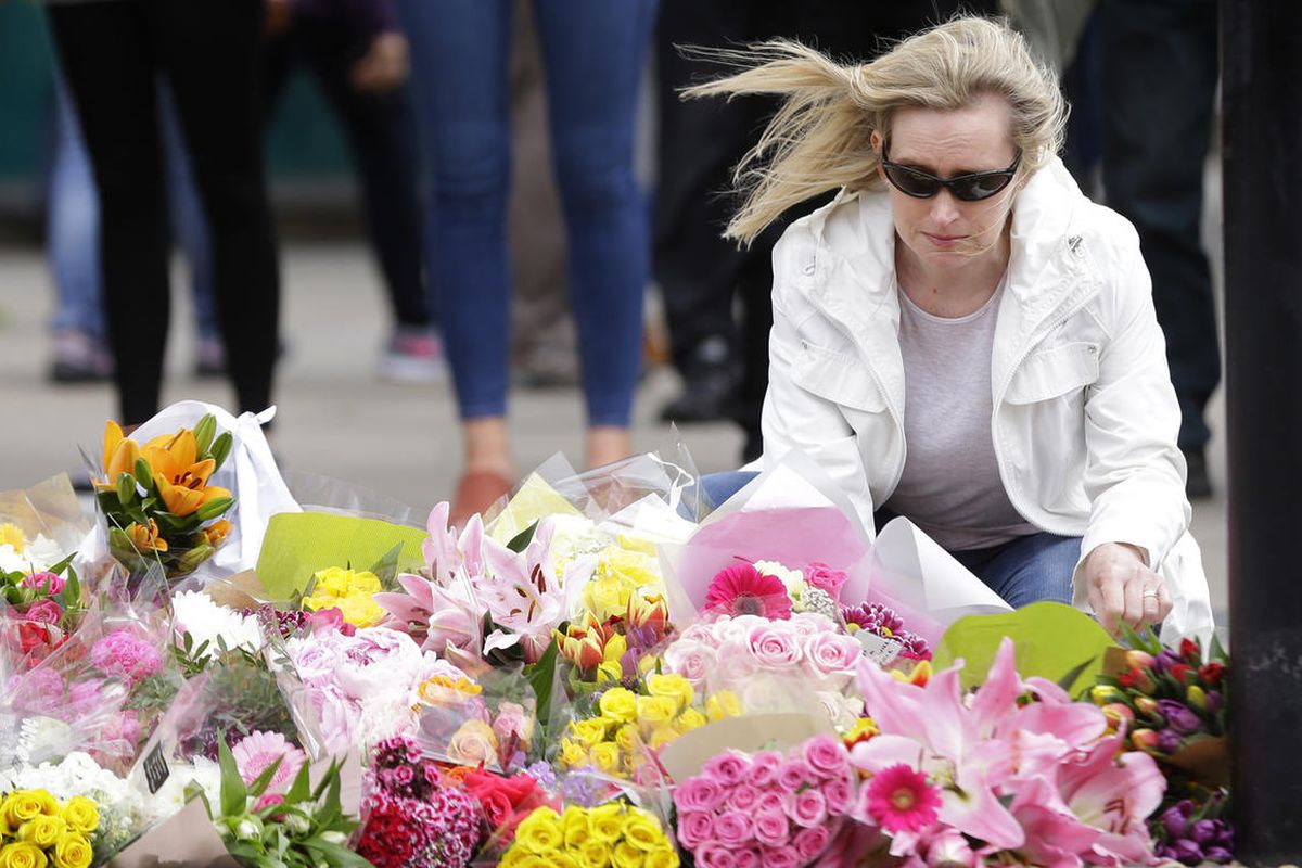 A woman prepares to leave a bouquet of flowers at a floral tribute in the London Bridge area of London, Monday, June 5, 2017. Police arrested several people and are widening their investigation after a series of attacks described as terrorism killed sever