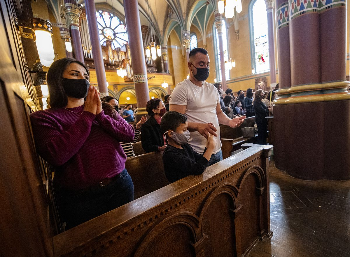 Guadalupe Navarro, left, Ivan Trejo and father Ivan Trejo attend a special reading of the Gospel and blessing of palm branches for Palm Sunday at theCathedral Madeleine in Salt Lake City on Sunday, March 28, 2021.