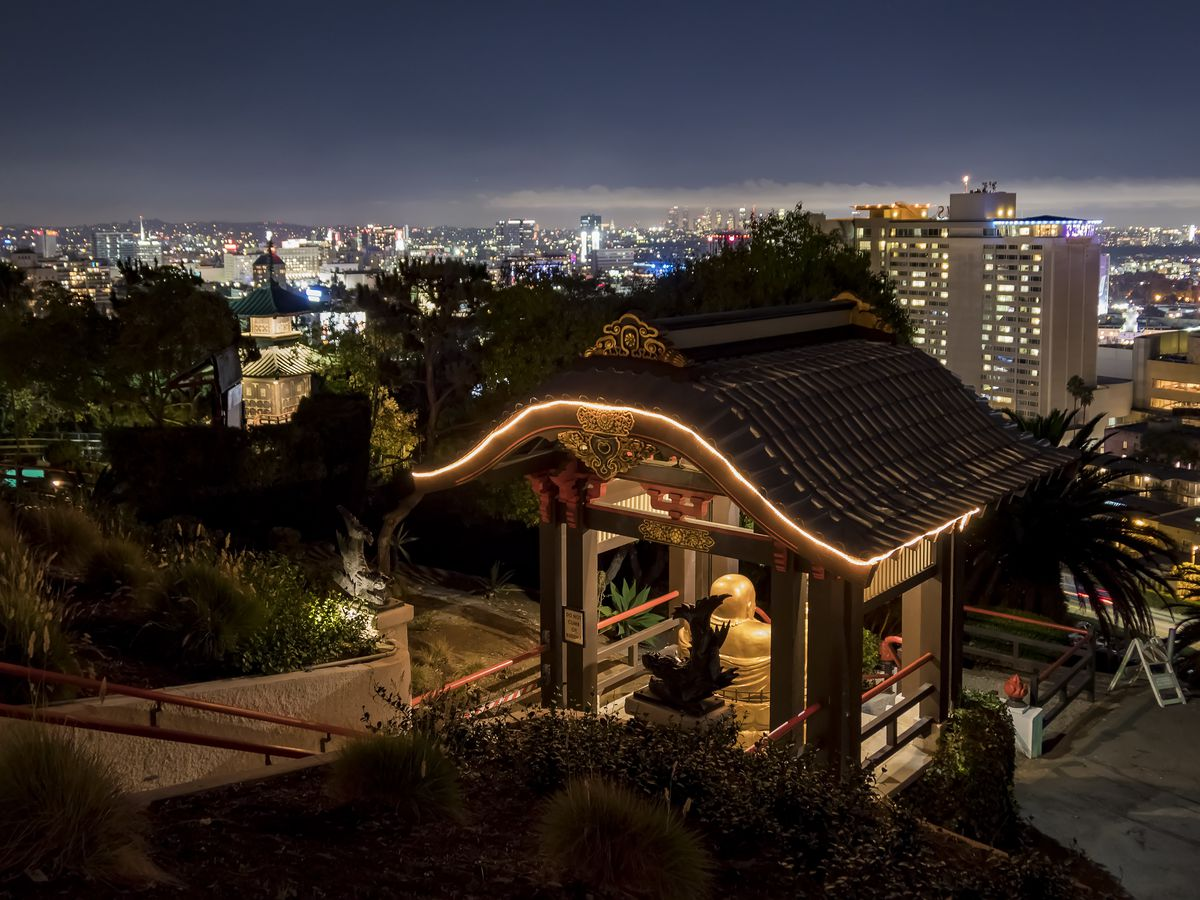 An illuminated pagoda with the bright lights of a cityscape in the background