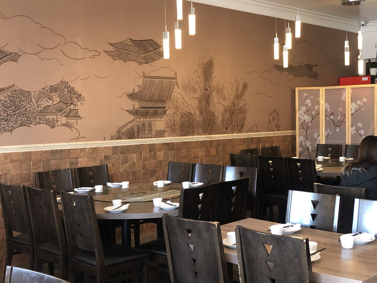 A wall mural of ancient Chinese buildings inside the dining room.