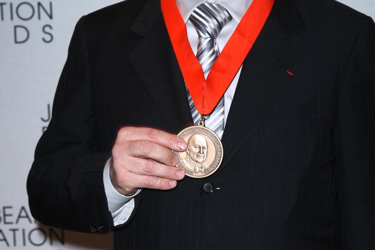 Photo shows someone holding up James Beard award medal, on ribbon around their neck.