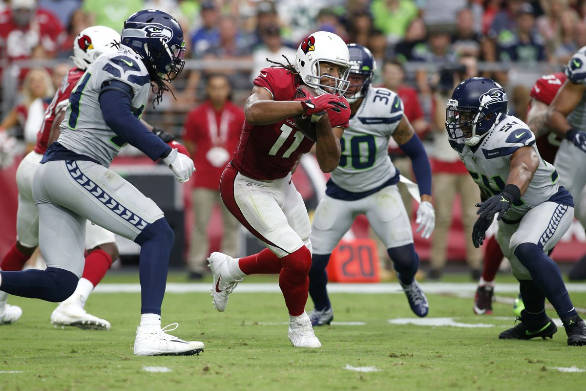 Arizona Cardinals Wide receiver Larry Fitzgerald runs with the ball between Seattle Seahawks' Ziggy Ansah and linebacker Bobby Wagner after a catch during the second half of the NFL football game at State Farm Stadium on September 29, 2019.