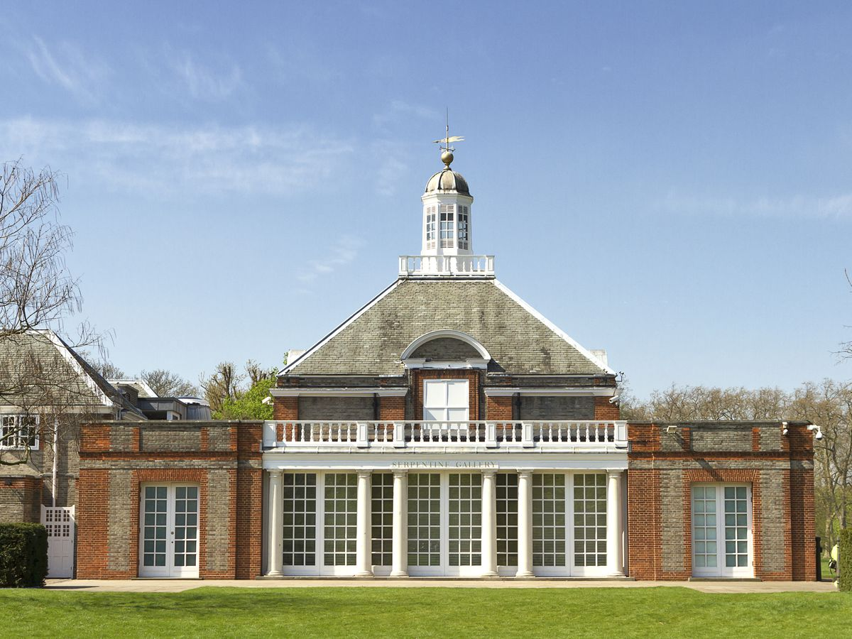 The exterior of the Serpentine Gallery in London. The facade is red brick with white columns and a roof with shingles.