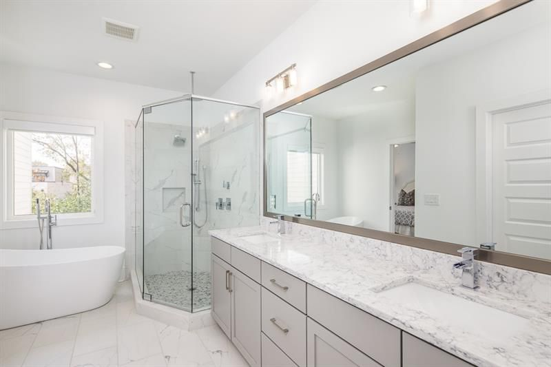 A white bathroom with a long countertop and shower.