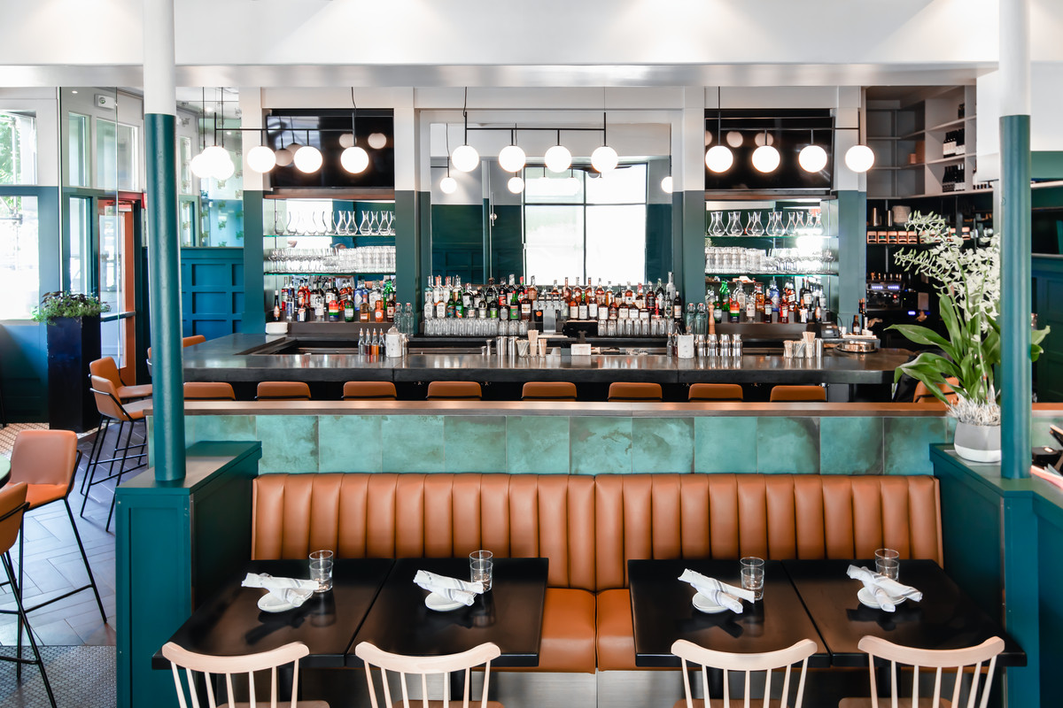 An interior shot of Black Lamb in the South End, featuring tan leather booths and mint green accents