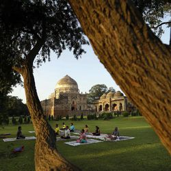In this Tuesday, Sept. 25, 2012 photo, Indians practice yoga at the sprawling grounds of Lodi Garden in New Delhi, India. Lodhi Garden in a posh neighborhood of south Delhi is a destination beloved by locals, with monuments like the tomb to 16th Century ruler Sikander Lodhi, the Bara Gumbad complex and several other structures with surviving traces of intricate designs.