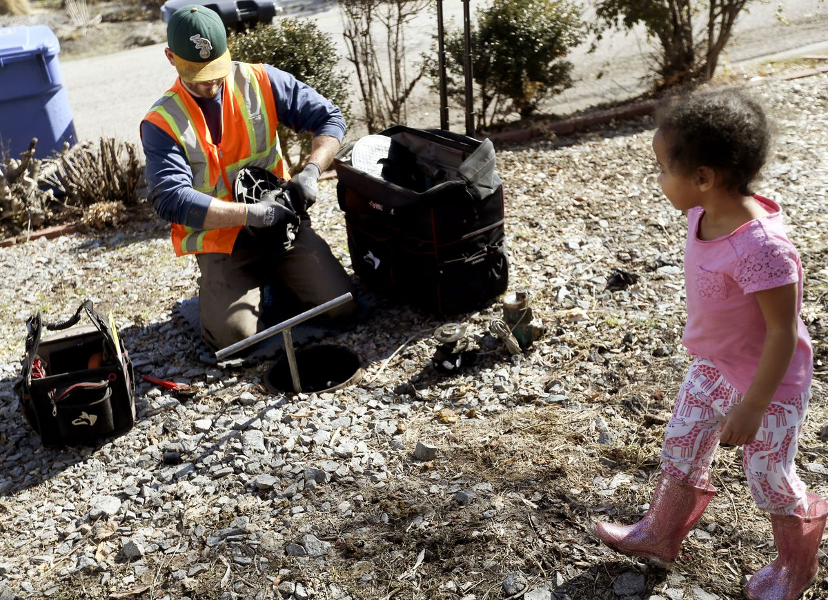 Cleo Naomi Brown, 3, watches as Robbie Giles, automated meter infrastructure technician for Salt Lake City Public Utilities, removes a water meter in Salt Lake City on Wednesday, Feb. 19, 2020. The Utah Division of Drinking Water is requesting additional money to step up compliance of public drinking water systems.