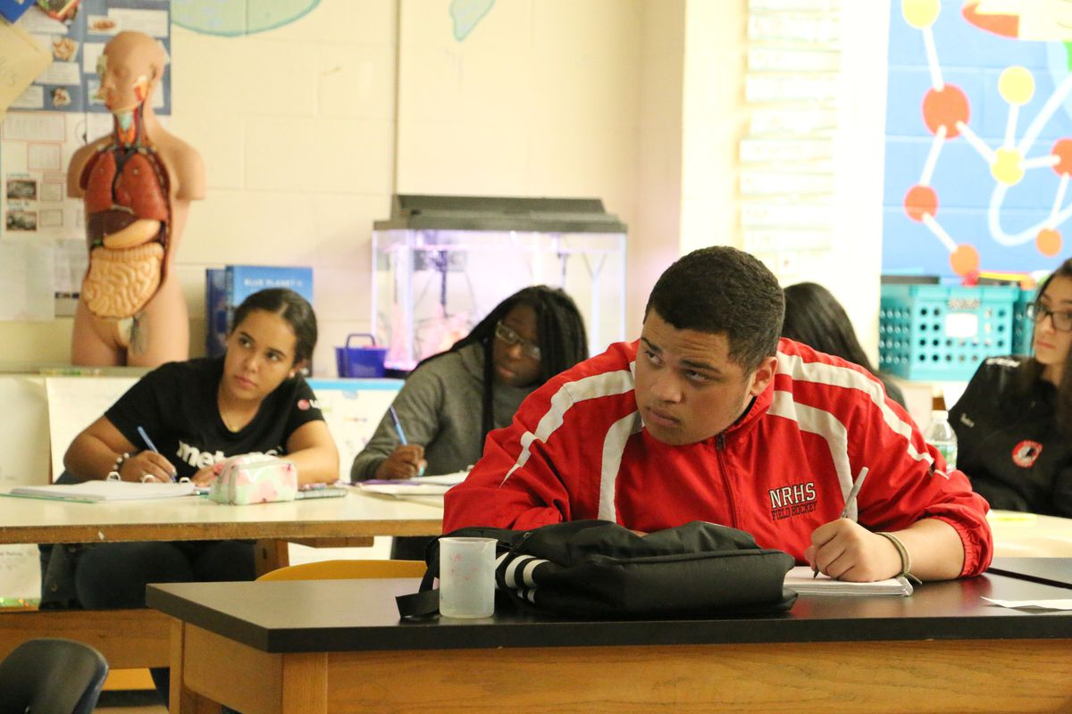 Hannah Olaniyi (center) and Gabriel De Oliveira take a college-level biology class at East Side High School.