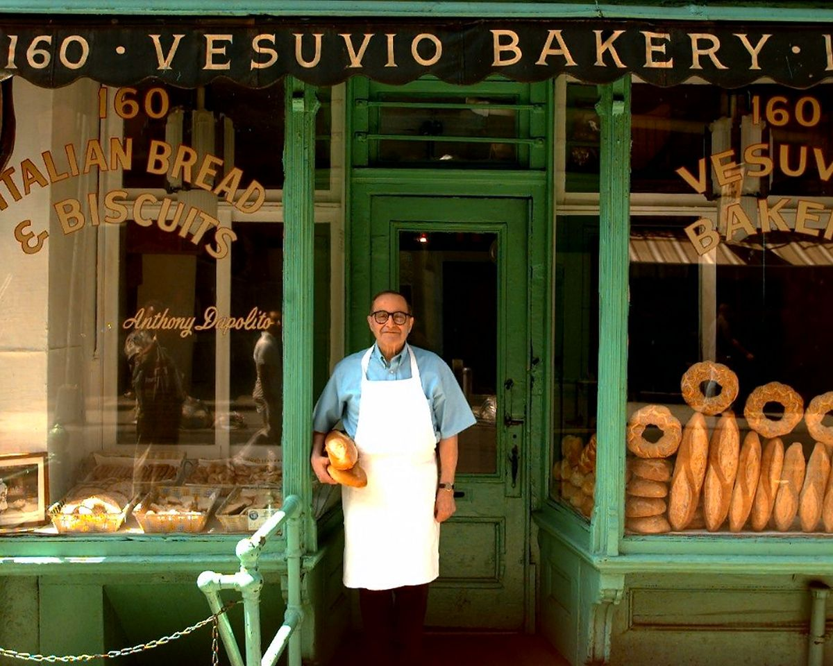 A baker in a white apron stands in front of Vesuvio Bakery in a historic photo.