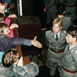 East German border policemen, right, refuse to shake hands with a Berliner who stretches out his hand over the border fence at the eastern site nearby Checkpoint Charlie border crossing point, in this  Nov. 10, 1989 file photo, after the borders were opened according to the announcement by the East German government. Monday, Nov. 9, 2009 marks the 20th anniversary of the fall of the Berlin Wall.