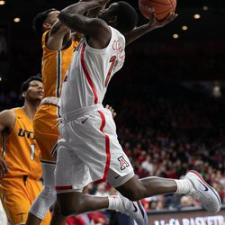 Arizona's Justin Coleman, right, tries to lay in the ball past UTEP defense during the Arizona-University of Texas El Paso game in McKale Center on November 14 in Tucson, Ariz.