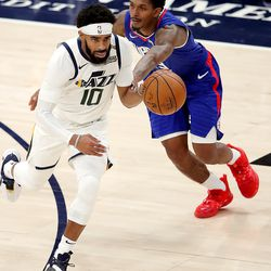 Utah Jazz guard Mike Conley (10) is fouled by LA Clippers guard Lou Williams (23) as the Utah Jazz and LA Clippers play in an NBA basketball game at Vivint Smart Home Arena in Salt Lake City on Friday, Jan. 1, 2021. Utah won 106-100.