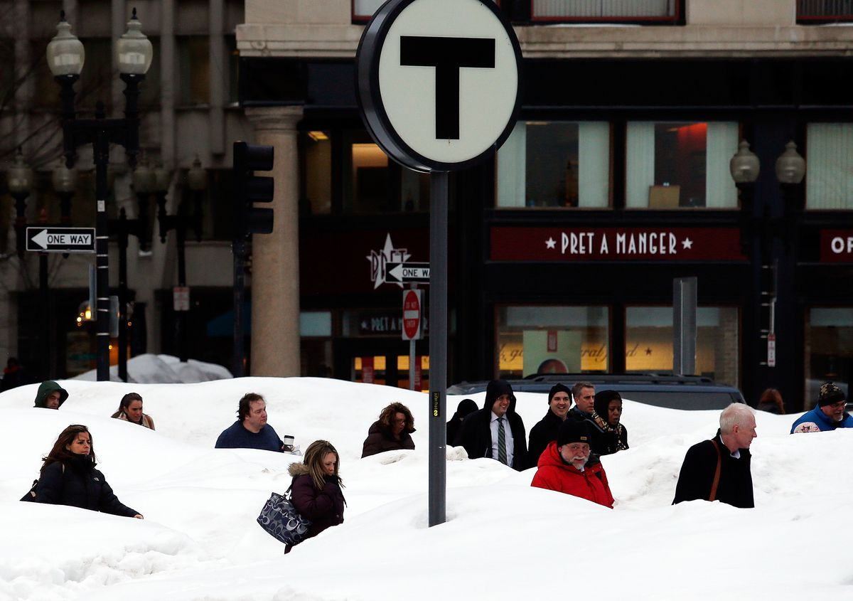 People traipsing about massive piles of snow, and there's a subway sign sticking out in the middle of the piles.