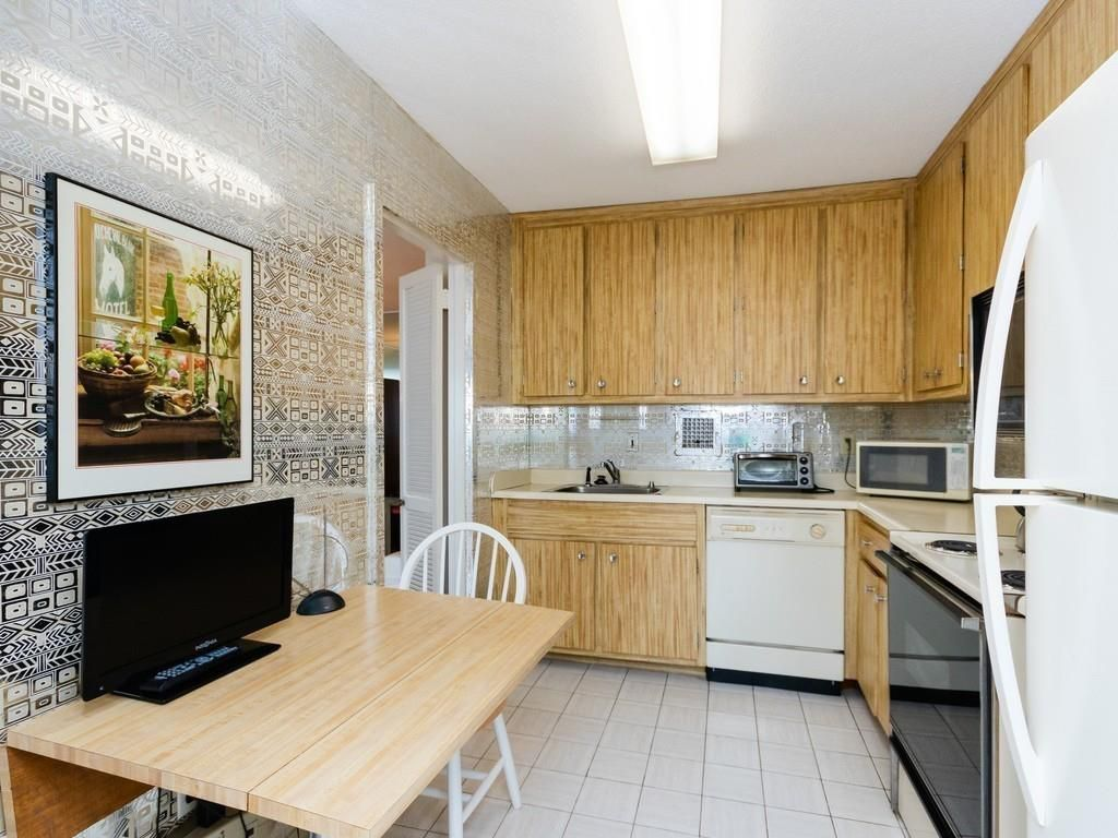 A small kitchen with a table and chairs, and there's a TV on the table.