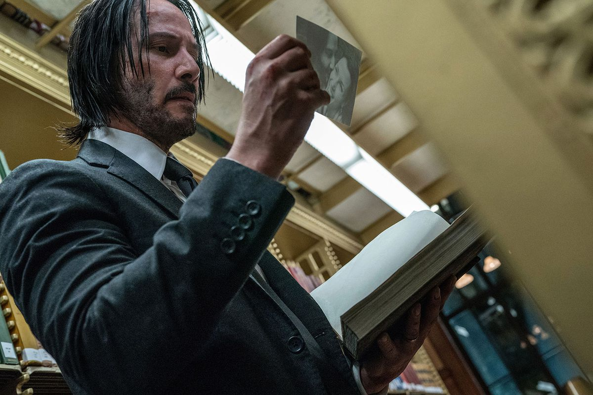 John Wick looks at a photograph in a still from John Wick: Chapter 3—Parabellum