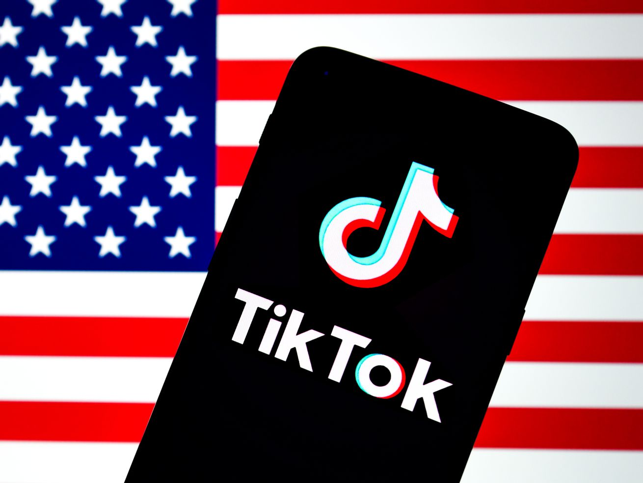 In this photo illustration, a TikTok logo is displayed on a smartphone with an American flag in the background.