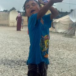 A young refugee pours water over his head in an effort to keep cool on a hot day in the Diavota refugee camp in northern Greece in July 2016.