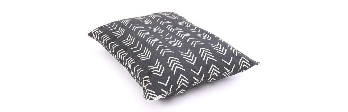 A dog bed which is decorated with a black and white geometric pattern.