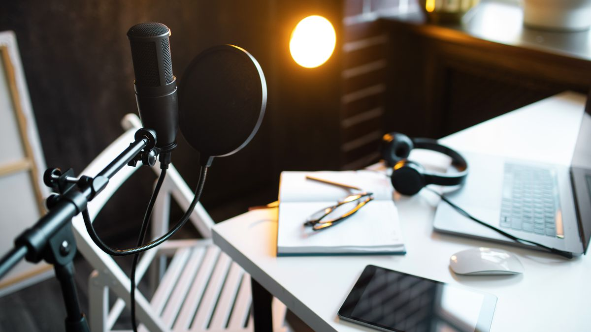 A desk set up with a computer, headphones, and a recording microphone.