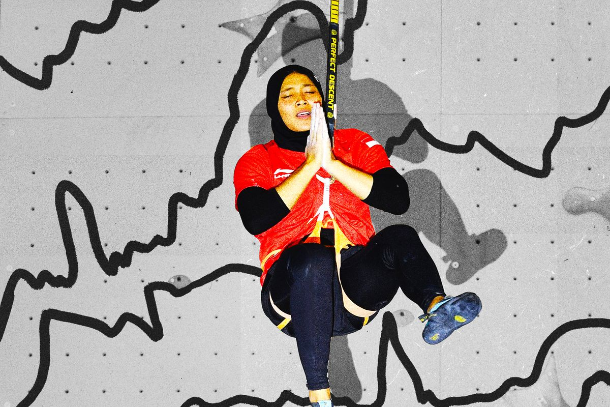 Indonesia's Aries Susanti Rahayu celebrates while suspended in her harness after winning gold in women's speed climbing at the 2018 Asian Games