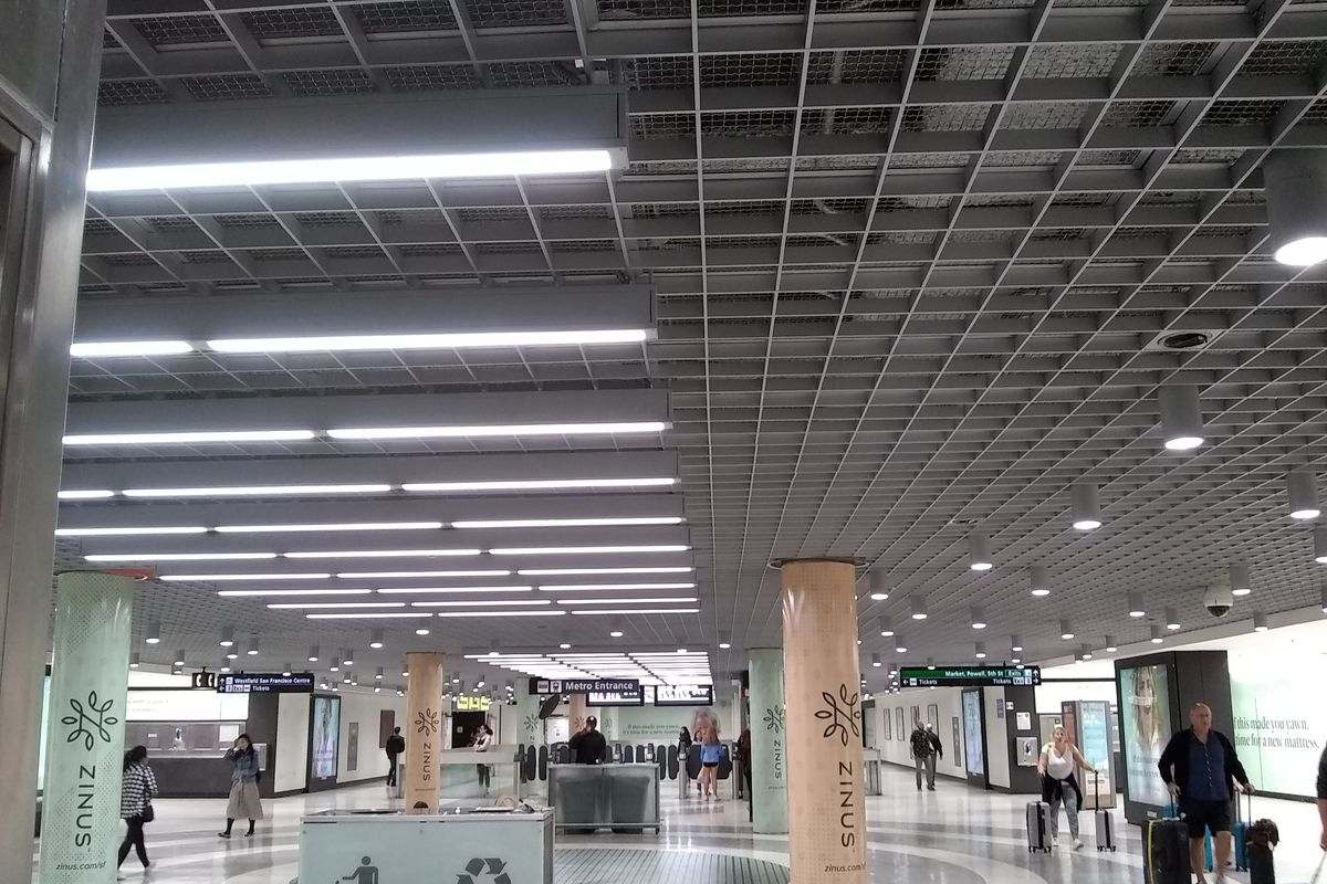 An underground subway station with white interiors and a grid-like metallic ceiling overhead.