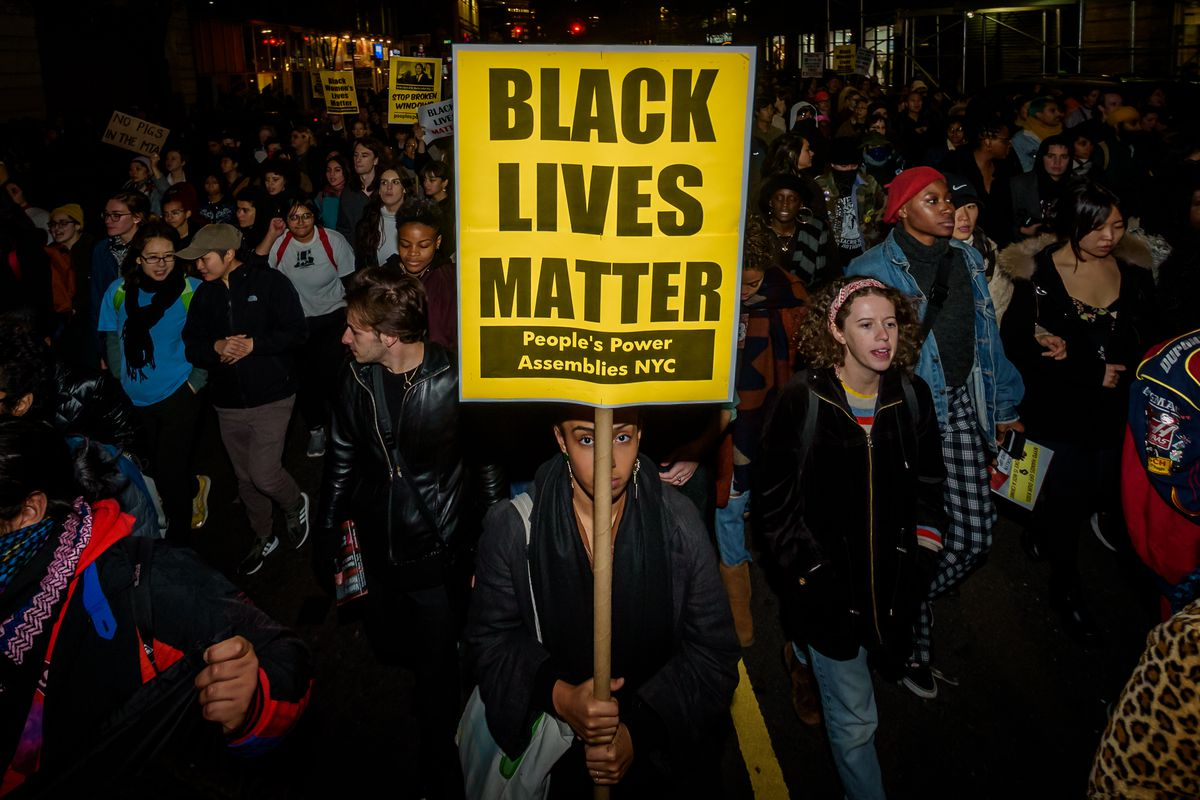"""A protester in a crowd holds a sign that reads, """"Black Lives Matter."""""""