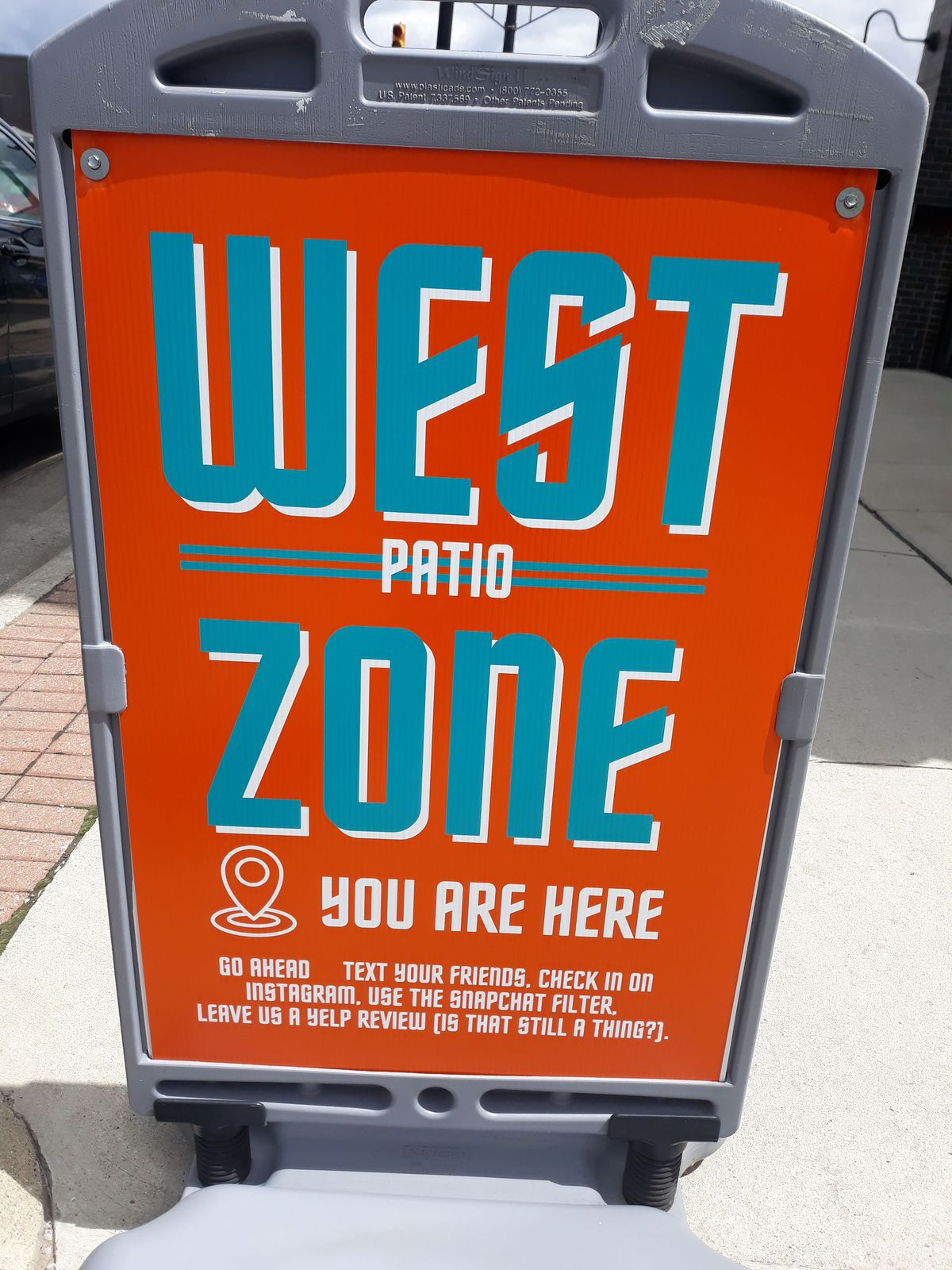 """A sidewalk signs in Ferndale reads """"West Zone, You Are Here"""" and indicates the social district for sidewalk drinking"""