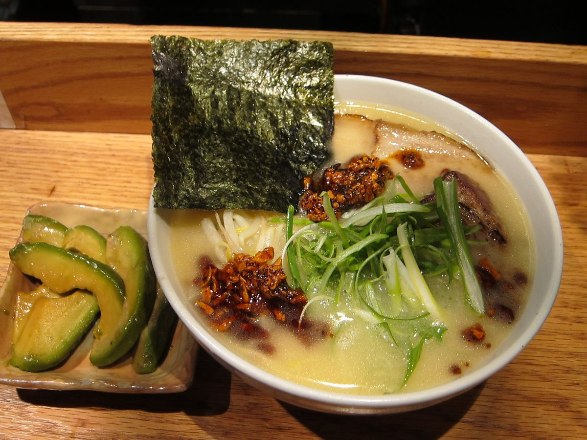 A bowl of ramen with a side of avocado