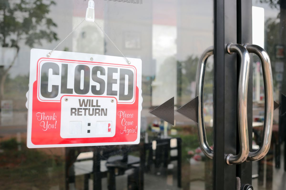 """A """"closed sign hanging on a glass door."""