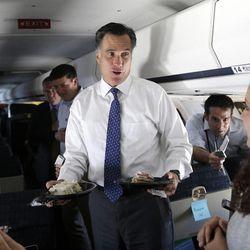Republican presidential candidate, former Massachusetts Gov. Mitt Romney wishes Ginger Gibson, national political reporter for Politico, right, a happy birthday on his campaign plane as it flies to Long Island, NY, Thursday, Sept. 13, 2012.