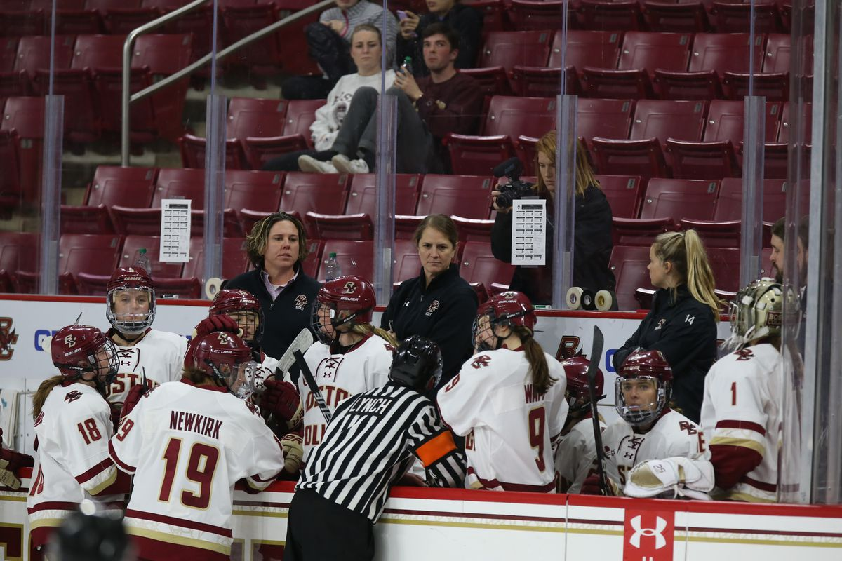 Boston College players gather around coaches Katie Crowley and Courtney Kennedy on the bench during a game.
