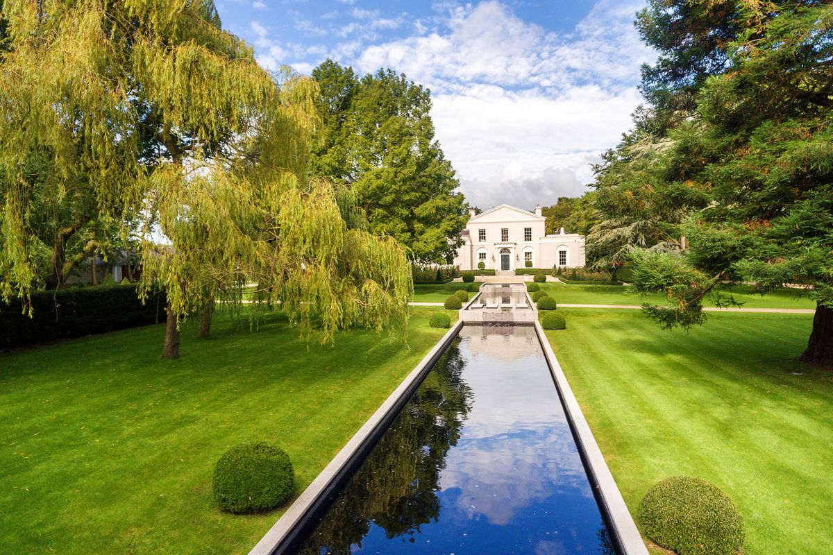 Neoclassical home on manicured lawns with a long tiered fountain flanked by topiaries leading up to it.
