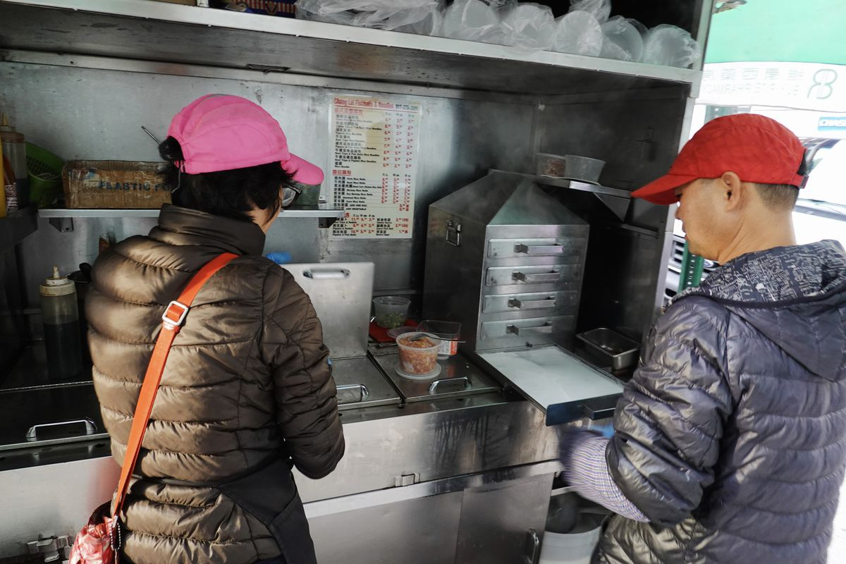 A woman in a pink hat and a man in a red hat work at a rice roll street food cart