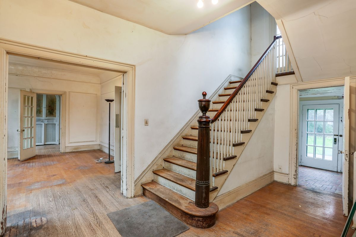 Foyer and staircase leading to second floor. The floors are discolored in numerous spots.