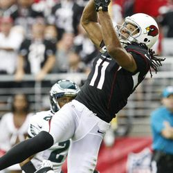 Arizona Cardinals' Larry Fitzgerald (11) makes a jumping touchdown catch in front of Philadelphia Eagles' Nnamdi Asomugha in the first half of an NFL football game on Sunday, Sept. 23, 2012, in Glendale, Ariz.